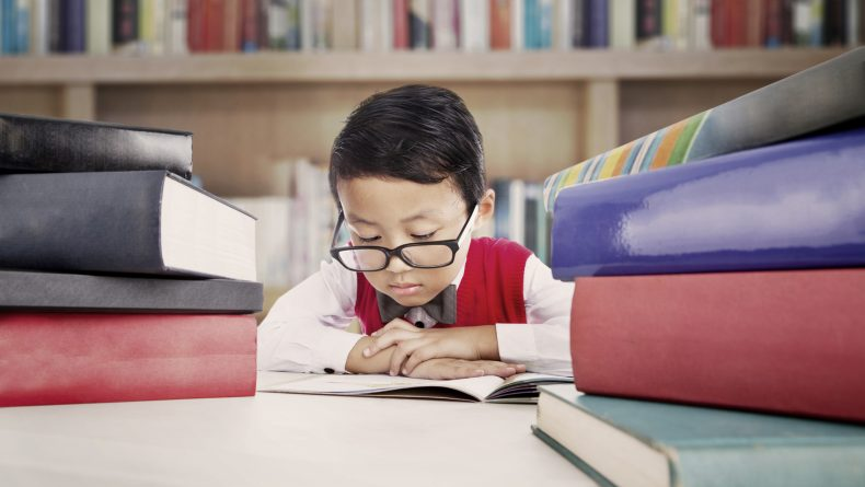 Portrait of asian elementary school student studying in the library