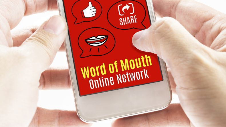 Close up Two hand holding smart phone with word of mouth online network word and icons, Digital concept.