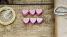 Condom, heart shapes and gift box on a wooden background