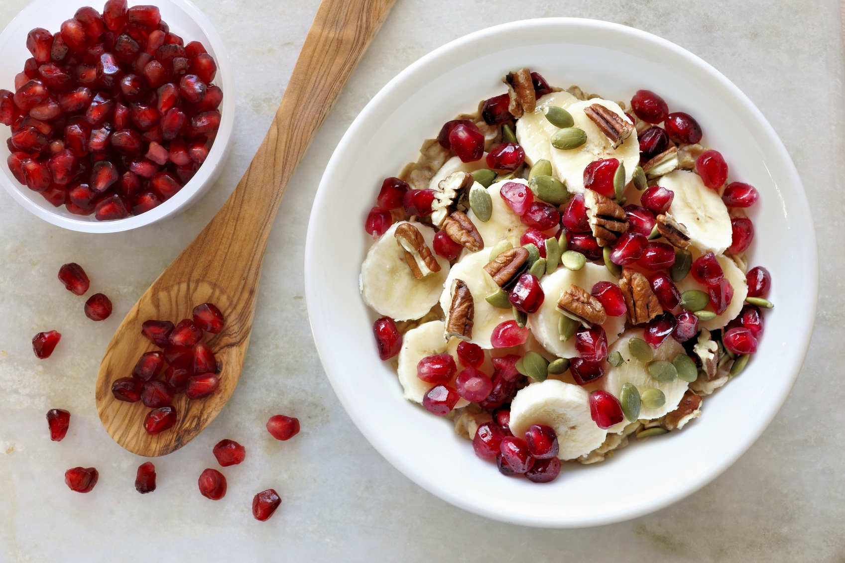 Healthy breakfast oatmeal with pomegranate, bananas, seeds and nuts