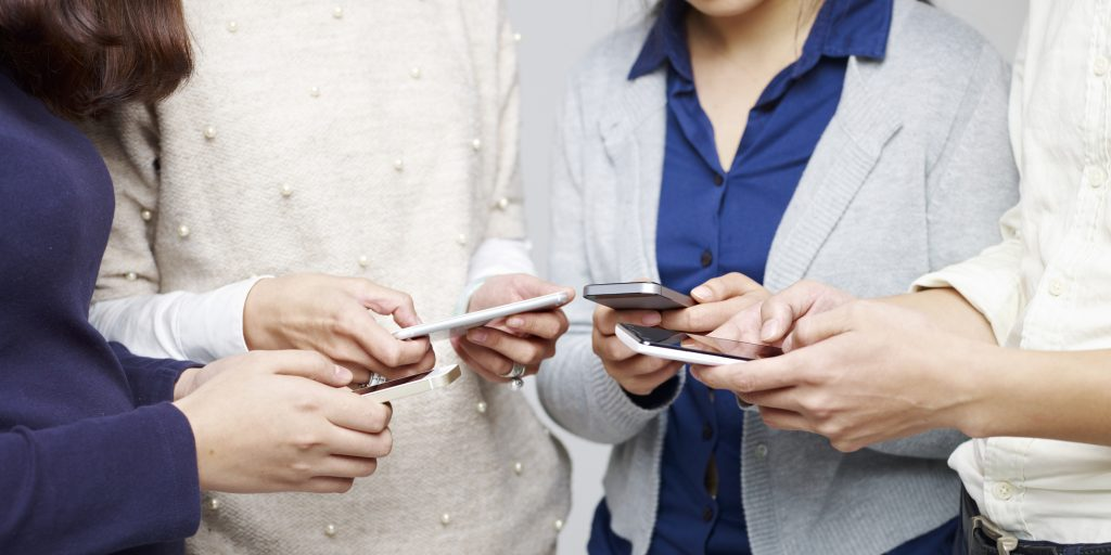 group of young people playing with cellphones together